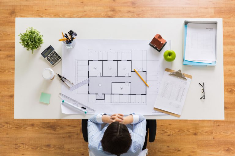 architect-with-house-blueprint-at-office-PDQRLAX